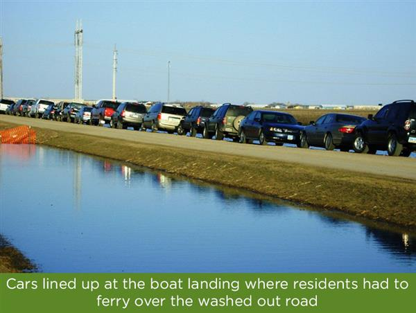 Cars lined up waiting to take the ferry across the flooded river.
