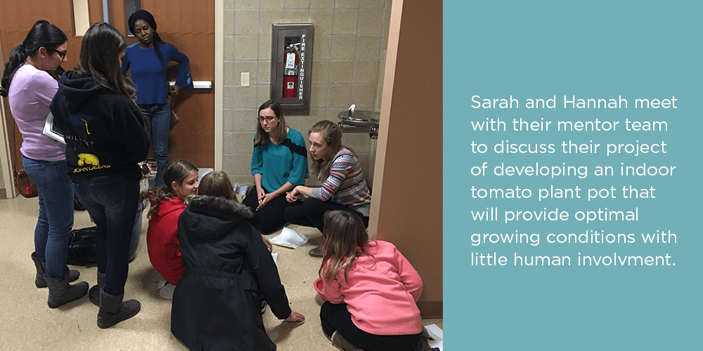 Hannah and Sarah meet with their mentor team to discuss their project.