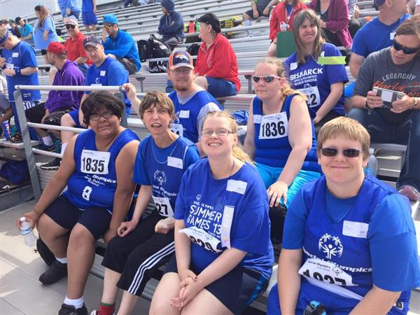 Special Olympics group on benches watching events