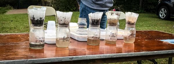 Different water filters at HEI's demonstration table at Waterfest